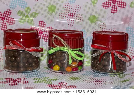 Three glass jars with ribbons and candy