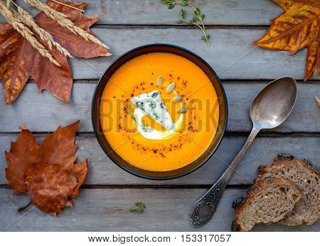 Hot pumpkin soup with blue cheese, herbs and multi-cereal bread on a wooden table. View from above
