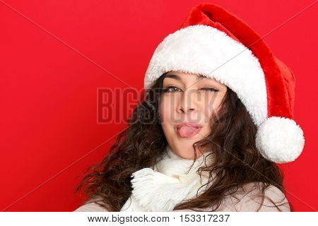 girl in santa hat portrait on red color background show tongue, christmas holiday concept, happy and emotions