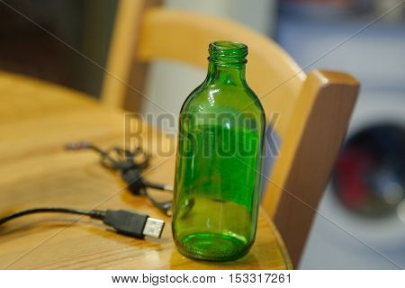 Still life of empty bottle and cables on a table
