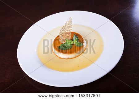 dessert cream brulee on the plate decorated with mint and caramel