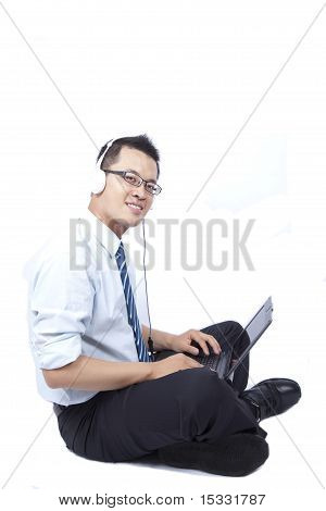 smiling young businessman sitting and using a laptop