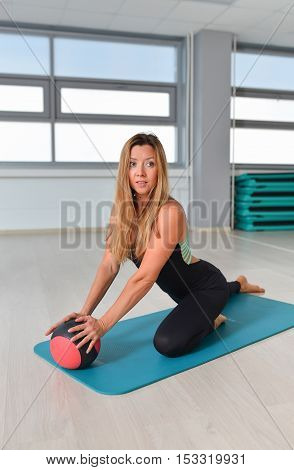 Fitness, sport, exercising lifestyle - fit woman in bodysuit posing on mat with medicine ball at gym.