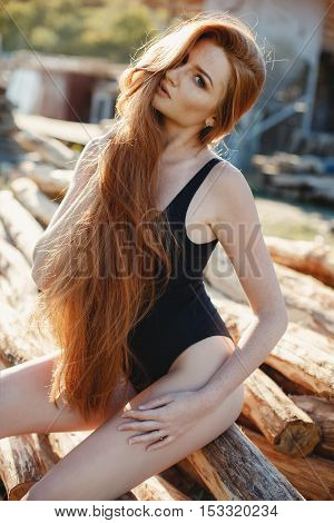 Portrait of sexy redheaded woman,long thick hair,the freckles on the face and body,big lashes and beautiful eyebrows,dressed in black closed swimsuit,slender beautiful figure posing outdoors in the summer in the countryside on a country ranch