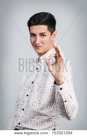 Young handsome man shows OK sign on the gray background