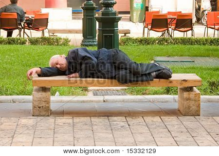 Homeless person sleeping on a bench
