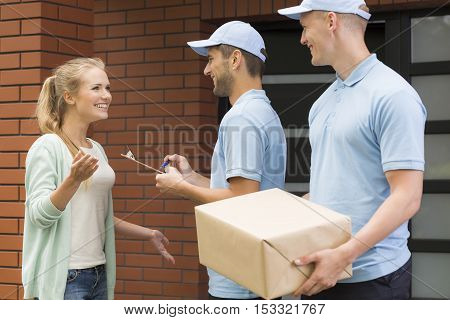 Two Professional Couriers Delivering A Package
