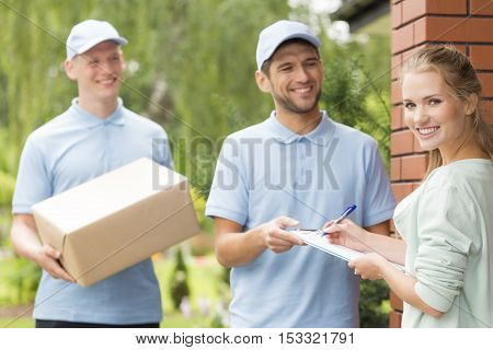 Couriers And Content Woman Signing A Form