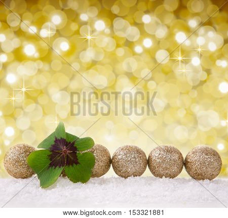 Christmas decoration with snow isolated on bokeh background.Defocused bokeh lights.Lucky symbols: four-leaf clover and balls.Green cloverleaf and decoration.