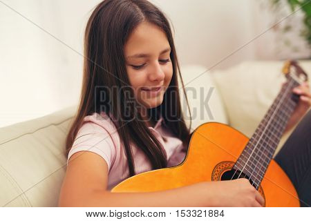 Cute little girl practicing her guitar lessons at home