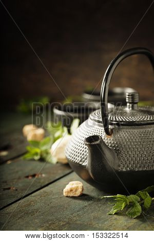 Japanese teapot and cups with mint tea on wooden background
