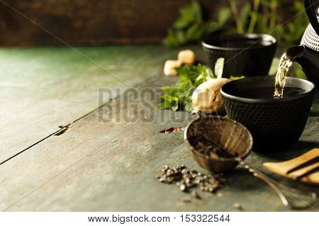 Japanese teapot and cups with mint tea on wooden background. Tea pouring into cup