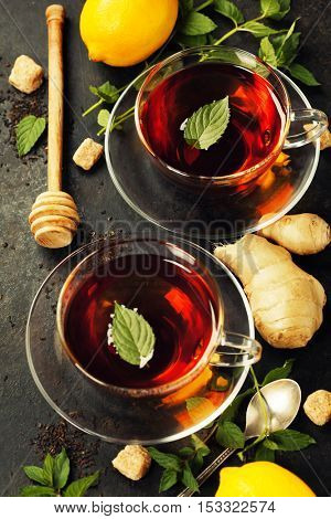 Hot tea cups with mint, lemon and sugar on rustic background