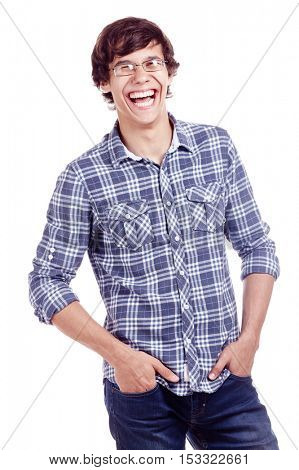 Young hispanic man wearing glasses, blue shirt with rolled up sleeves and jeans standing with hands in pockets and loudly laughing isolated on white background - laughter concept