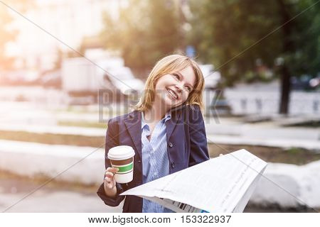Portrait of business woman with to go coffee and newspaper in hands
