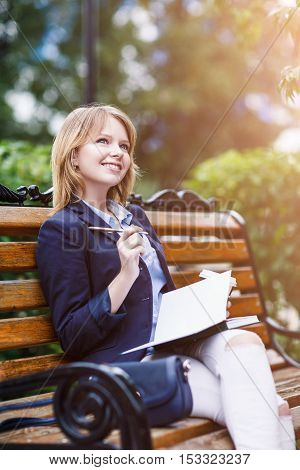 Young business woman sitting on the bench with diary in autumn park