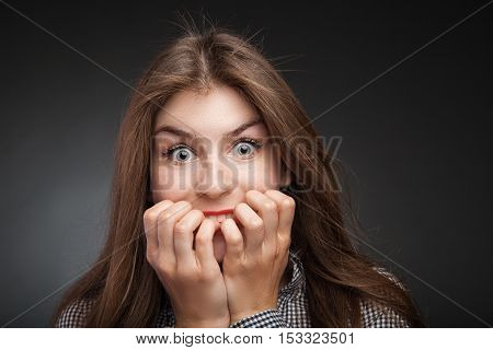Amazed woman biting nails. Studio headshot on black vignette background.