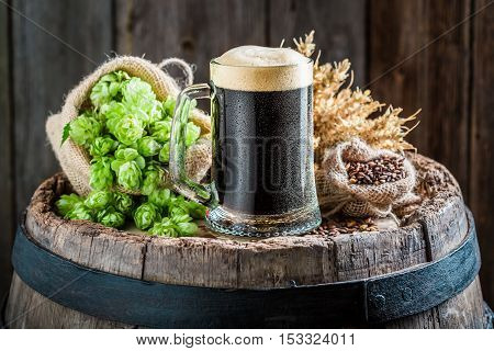 Dark Beer With Foam, Wheat And Hops On Old Barrel