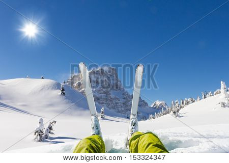Detail of alpine skier legs, watching the valley panorama. Winter equipment, vacation concept, copyspace for text