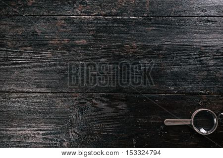 Simple magnifying glass on the dark wooden surface. Flat lay