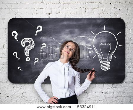 Pretty thoughtful girl on brick background with question marks and light bulb sketch on chalkboard. Idea concept