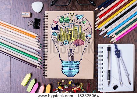 Top view of wooden desktop with creative colorful business sketch inside light bulb and supplies. Idea concept