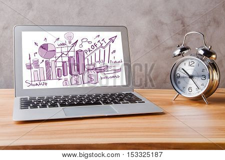 Laptop with creative financial sketch placed on wooden desktop with silver alarm clock. Concrete background. Business concept