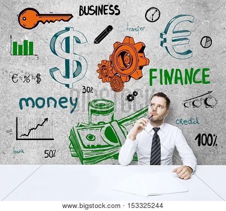 Thoughtful and confused young businessman at workplace with creative financial sketch on concrete wall. Success concept