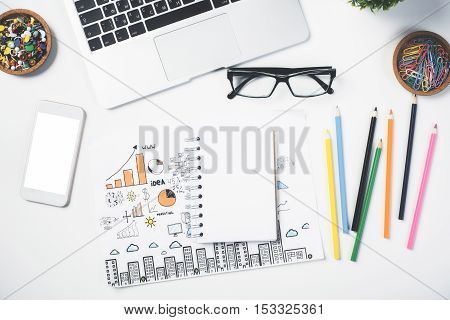 Top view of bright desktop with blank white smartphone spiral notepad colorful supplies glasses and business sketch. Mock up