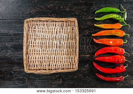 Row of hot peppers gradually changing their color from green to dark red with wicker tray