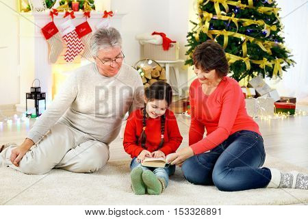 Little girl and her grandparents reading book in living room decorated for Christmas