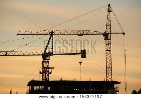 installation of monolithic reinforced concrete building with the help of two cranes at sunset