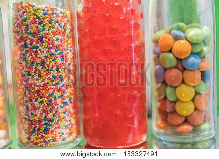 horizontal image of little bottles of assorted decorative christmas candy sprinkles standing in a row on a red book adorned with pine cones and cranberries on burlap background