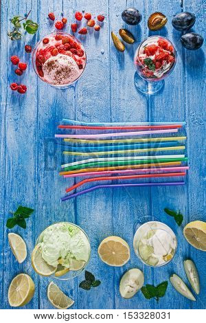 Lemon, strawberry, melon icecream and plum sorbet served in glass bowls over blue wooden background
