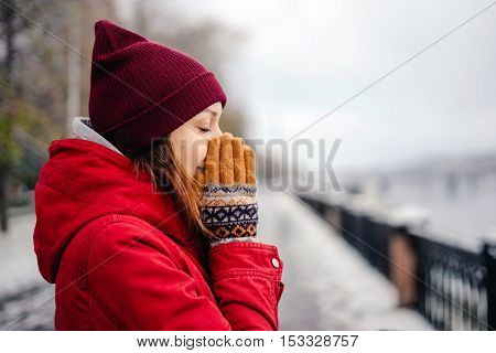 Girl presses the hands of her nose his hands in mittens cold autumn day the first snow. Girl walks in the park in a red coat