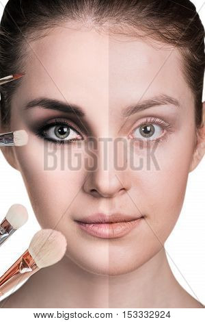 Beautiful woman with smokey eyes make-up and brushes near face, over white background