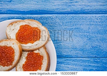 Toasts with salted salmon roe over sky-blue wood plank background. Closeup. Flat lay