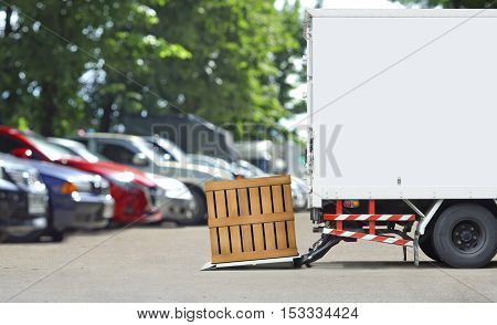 transportation and logistics concept - Delivery truck parking to delivery parcel wood box with wood wall and copyspace
