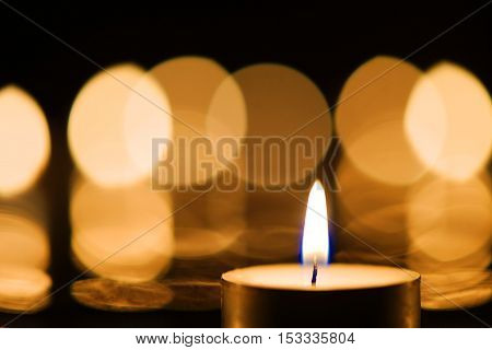 Close-up of a burning candle against bokeh background