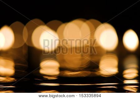 Close-up of golden candlelight bokeh with reflection