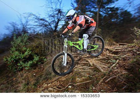 Um homem jovem, montando um estilo de descida de bicicleta de montanha