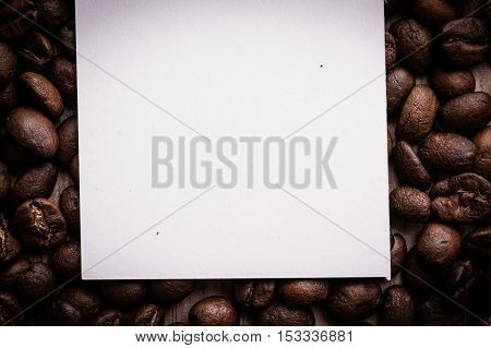 roasted coffee beans with black paper on wooden background can be used as a background