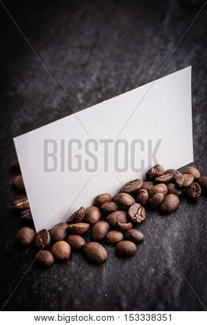 roasted coffee beans with blank paper on dark background can be used as a background