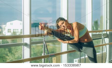 Fitness woman stretching in the gym. Barre.