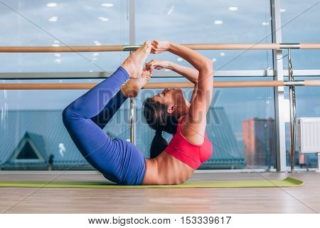 fitness, sport, training and lifestyle concept - Young woman doing yoga exercises on yoga mat at gym