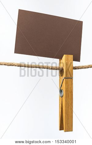 Wooden clip with a sign hanging on a rope on a white background