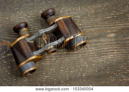 Old binoculars lying on a wooden board