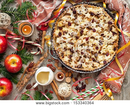 Christmas apple pie with stars pattern on a rustic decorated tabletop.