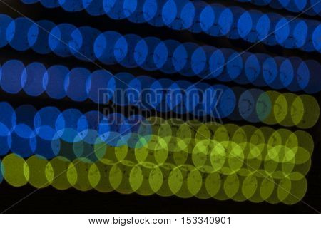Blurred abstract running LED lights in the colors of the flag of Ukraine. Color Bokeh at Night.