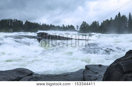 Cascades of water in the big river. Rocks and cliffs break the speed. Forests both sides.
